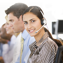 photo of a woman with headphones on in a call center